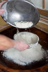 そば粉をふるいにかける料理人の手の写真素材 [FYI01607955]