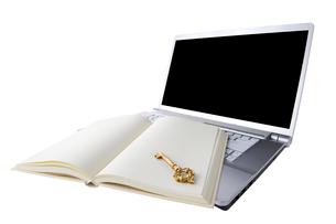 白紙の本に置かれた鍵とノートパソコンの写真素材 [FYI01608915]