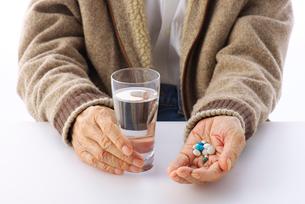 水と薬を持つシニアの写真素材 [FYI01609691]