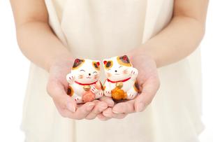 招き猫を持つ女性の手の写真素材 [FYI01610643]
