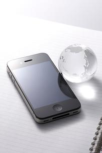 ノートに置かれたスマートフォンと地球儀の写真素材 [FYI01611758]