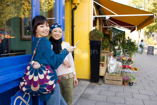 ロンドンの街角で携帯を見る20代女性2人の写真素材 [FYI01613702]