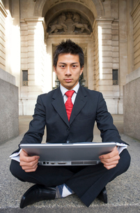 座ってパソコンを抱えるビジネスマンの写真素材 [FYI01613780]