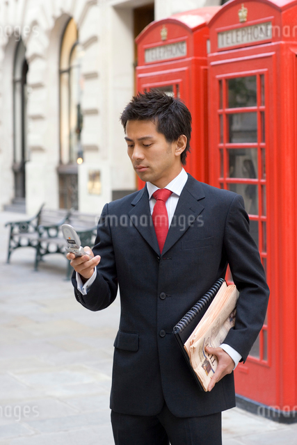 電話ボックスの前に立つビジネスマンの写真素材 [FYI01613918]