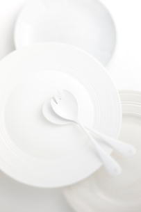 重ねた白い皿にサラダフォークとスプーンの写真素材 [FYI01613930]