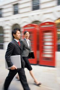 電話ボックスの前を歩く男女の写真素材 [FYI01614207]