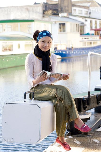 ロンドンの川辺で本を読む日本人女性の写真素材 [FYI01614482]