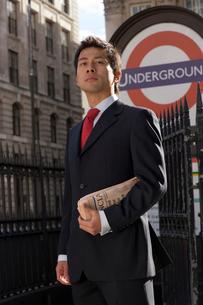 ロンドンの地下鉄入口で新聞を持って立つビジネスマンの写真素材 [FYI01614627]