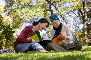 公園で本を読む20代女性2人の写真素材 [FYI01614690]