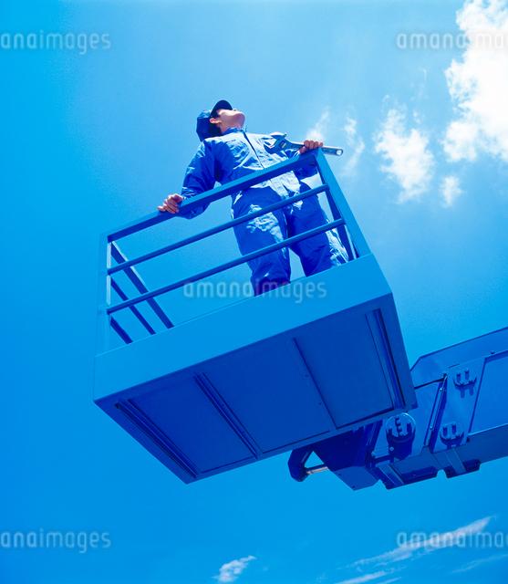 青空とクレーンに乗る作業員の写真素材 [FYI01614760]