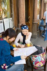 ロンドンのカフェで地図を広げる日本人女性2人の写真素材 [FYI01614772]