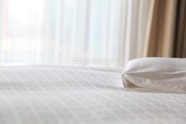 光の入る部屋のベッドと白いシーツの写真素材 [FYI01614919]