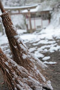 雪の積もった神社の境内に置かれた竹ぼうきの写真素材 [FYI01615933]