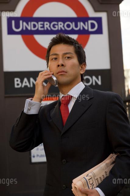 ロンドンの地下鉄入口で携帯をかけるビジネスマンの写真素材 [FYI01615965]