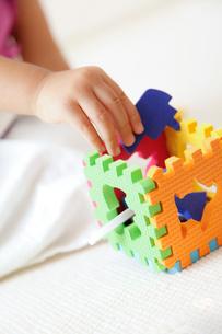 カラフルな知育玩具で遊ぶ幼児の手の写真素材 [FYI01615966]