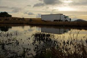 夕暮れの池のほとりを走るトレーラーの写真素材 [FYI01616018]