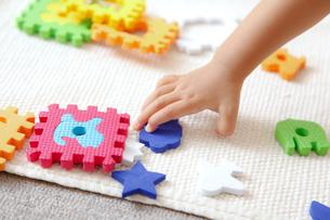 カラフルな知育玩具で遊ぶ幼児の手の写真素材 [FYI01616077]