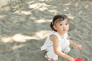 砂場でシャボン玉を見上げる女の子の写真素材 [FYI01616157]