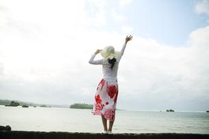 海辺で空に向かって右手を持った女性の写真素材 [FYI01616270]