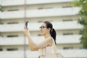 スマートフォンを操作するビジネスウーマンの写真素材 [FYI01616453]