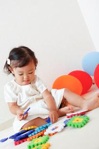 カラフルな知育玩具で遊ぶ女の子の写真素材 [FYI01616502]