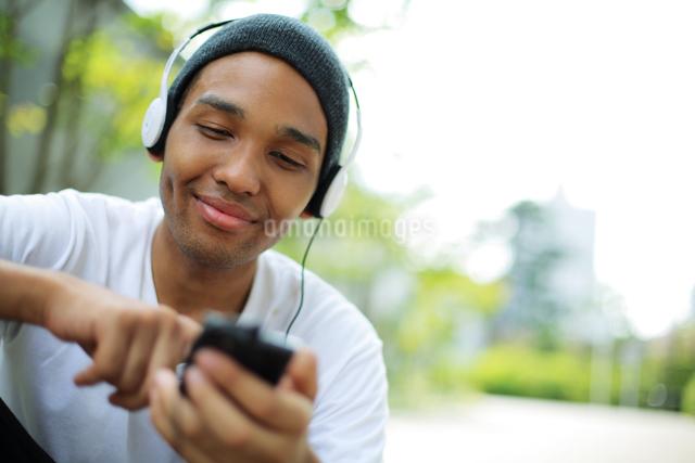 スマートフォンで音楽を聞いている男性の写真素材 [FYI01616527]