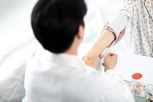 患者の状態をチェックしている外科医イメージの写真素材 [FYI01616632]