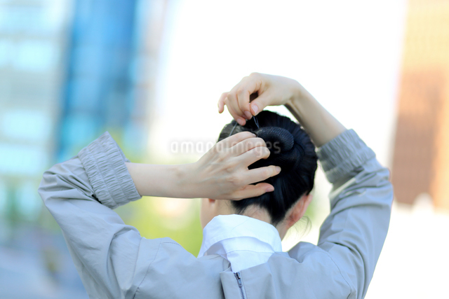 ヘアピンでヘアスタイルを固定している女性の写真素材 [FYI01616734]