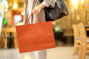 右手でショッピングバッグを持っている女性の写真素材 [FYI01616742]