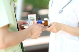 医療用具の受け渡しをする看護補助者の写真素材 [FYI01616878]