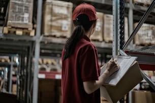 商品チェックをしている物流センターのスタッフの写真素材 [FYI01616881]