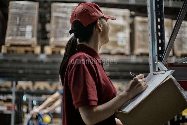 商品チェックをしている物流センターのスタッフの写真素材 [FYI01616892]