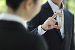 砂時計を持っているビジネスマンの写真素材 [FYI01616900]