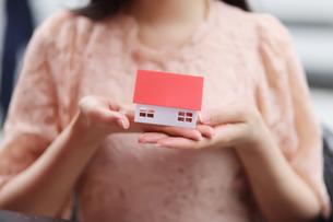 家の形のモデルを持っている女性の手の写真素材 [FYI01616949]