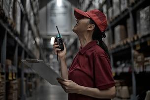 無線機を持って倉庫で働いている女性の写真素材 [FYI01616950]