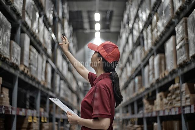 工場の中で製品チェックしている女性の写真素材 [FYI01616975]