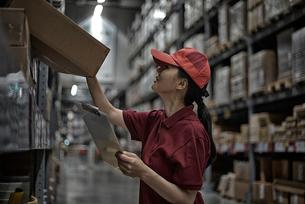 チャートを持って商品をチェックしている女性の写真素材 [FYI01616999]