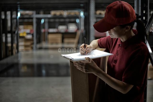 倉庫の中でメモしている物流センターのスタッフの写真素材 [FYI01617005]