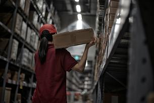 倉庫で商品のボックスを運んでいる女性の写真素材 [FYI01617055]