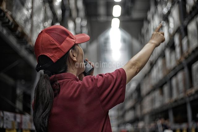 トランシーバーで通信している、倉庫の中の女性の写真素材 [FYI01617089]