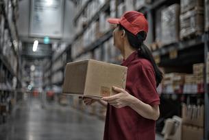 物流倉庫の中で商品ボックスを持っている女性の写真素材 [FYI01617242]