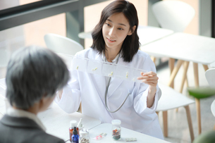 製薬会社の営業担当者と相談する女医の写真素材 [FYI01617317]