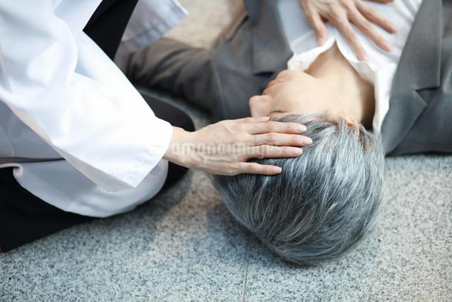頭で熱を測っている女性医師の写真素材 [FYI01617322]
