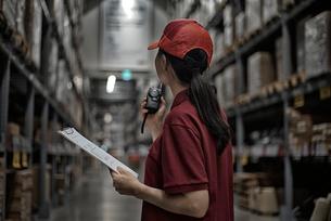 書類と無線機を持って倉庫で働いている女性の写真素材 [FYI01617381]