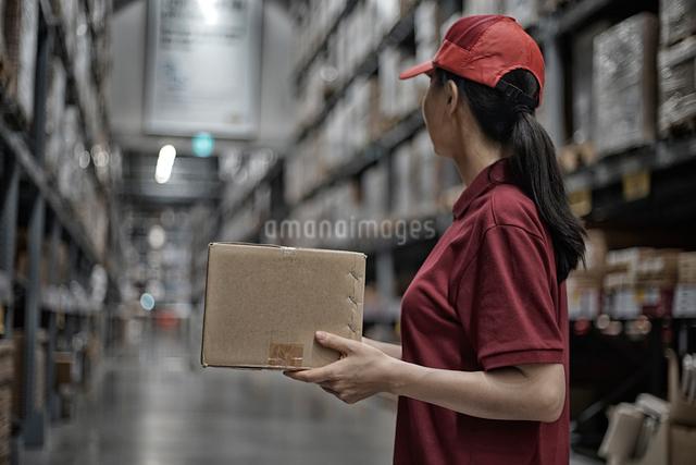 物流倉庫で商品のボックスを運んでいる女性の写真素材 [FYI01617547]