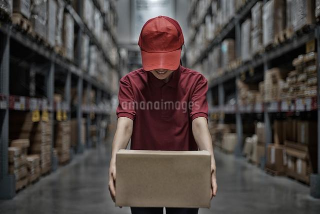 商品ボックスを持って挨拶している女性の写真素材 [FYI01617630]