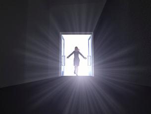 暗闇に開いたドアから駆け出す女性のイラスト素材 [FYI01617698]