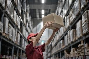 物流倉庫で商品のボックスを運んでいる女性の写真素材 [FYI01617758]