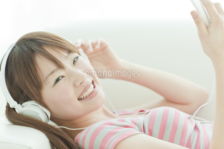 ソファーで音楽を聴く若い日本人女性の写真素材 [FYI01619472]