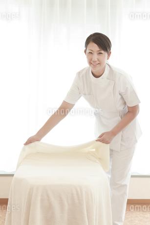 ベッドを整えるエステシャンの写真素材 [FYI01619528]